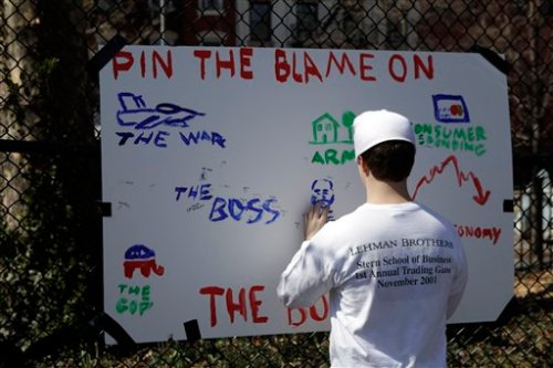 "A participant in the Unemployment Olympics wearing a Lehman Brothers shirt, tries to find the boss in the game ""Pin the Blame on the Boss"" in New York, Tuesday, March 31, 2009. (AP Photo/Seth Wenig)"